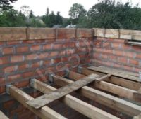 деревянные балки перекрытия и кладка стен второго этажа дачного дома
